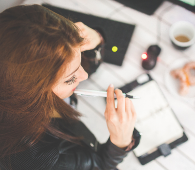 Image shows a woman biting the end of a pen whilst looking at a notebook