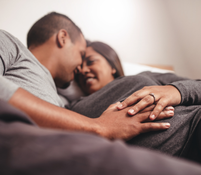 Image shows a couple lying down, with both their hands on the woman's pregnant abdomen.