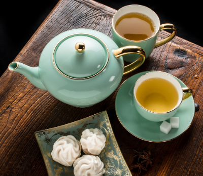 A mint green teapot, two cups and some cakes on a wooden table top.