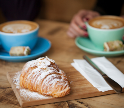 Image shows a wooden table top with two mugs of coffee and a pastry in the foreground.