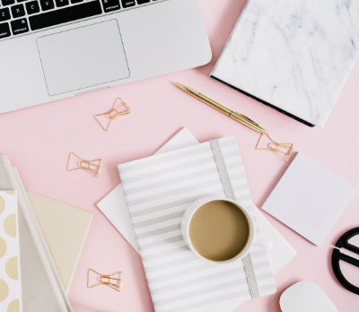 A pink table top showing a laptop, notebook, paperclips, pen and a cup of coffee.