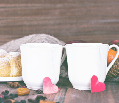 Two cups, side by side with small paper hearts in front of each.