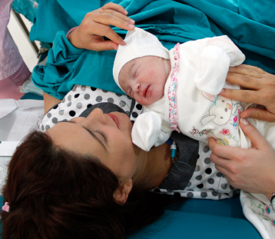 Image shows a woman post caesarean birth, holding her baby with some help from another pair of hands.