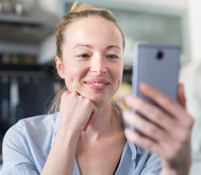 Image shows a woman holding her phone up to have a video call