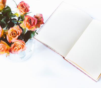 Image shows an open notebook and a jar containing peach coloured roses.